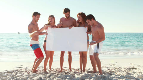 Friends holding blank poster at the beach Live Action