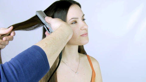 Girl getting long hair ironed Footage