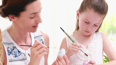 Mother and daughter painting easter eggs Footage