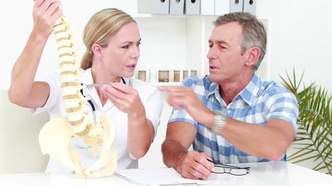 Doctor Explaining Anatomical Spine To Her Patient stock footage
