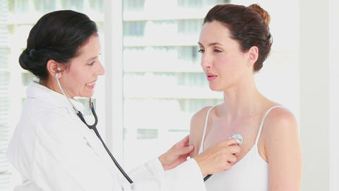 Doctor listening to patients chest with stethoscope Footage