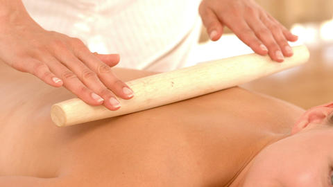 Beautiful blonde enjoying a bamboo roller massage Footage