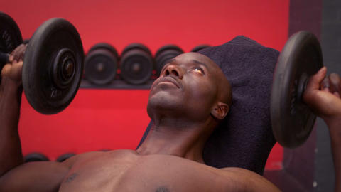 Fit man lying on exercise table holding dumbbell Footage
