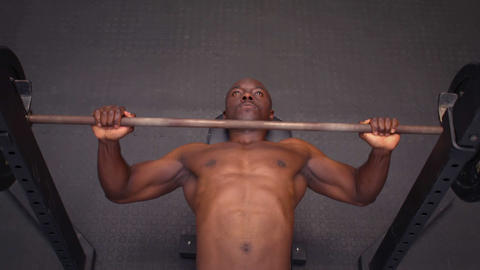 Concentrated fit man holding barbell lying on exercise mat Footage