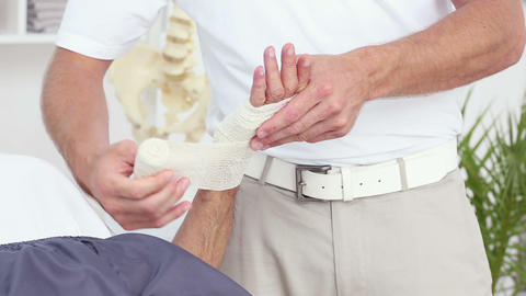 Doctor Bandaging His Patients Hand stock footage