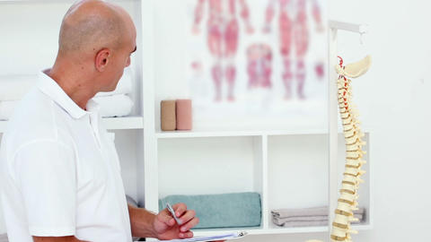 Doctor Looking At Spine Model And Taking Notes stock footage