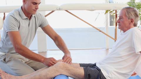 Doctor Massaging His Patients Knee stock footage