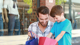 Father And Son Looking In Shopping Bag stock footage