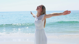 Happy blonde woman with arms outstretched at the beach Footage