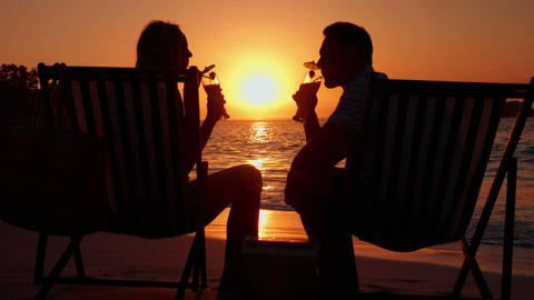 Couple drinking couple during the sunset on the beach Footage