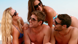 Group of smiling friends in swimsuits chatting on the beach Live Action