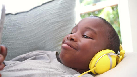 Little boy listening to music on the couch Footage