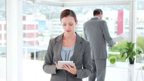 Businesswoman using tablet computer with her colleagues behind Footage