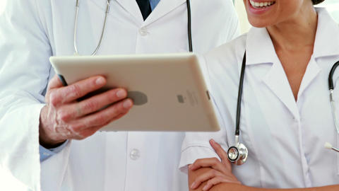 Happy doctors looking at tablet computer Live Action