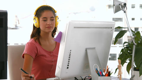 Casual businesswoman working on computer and listening music Footage