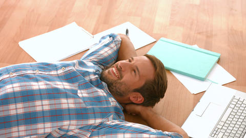 Happy handsome man lying on floor Live Action