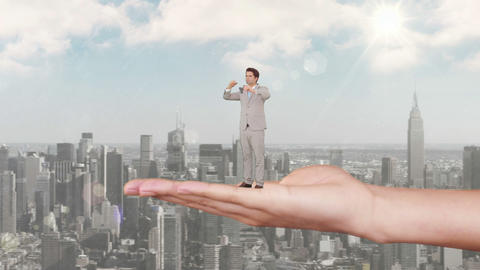 Hand holding standing businessman looking out above scyscrapers Animation