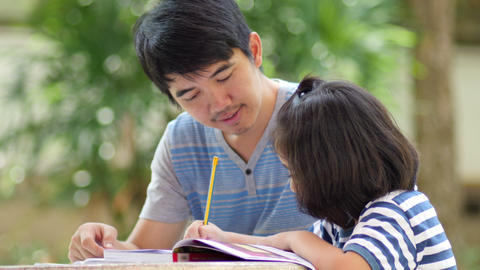 Little Asian girl with father doing homework on the table Footage