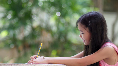 Little Asian girl doing homework in the garden at home Footage