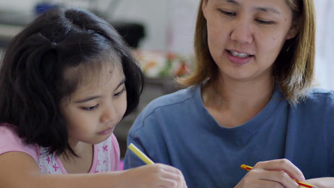 Little Asian Girl With Mother Doing Homework stock footage