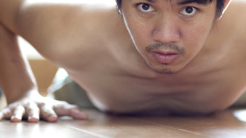 Thin Asian man exercise does pushups, wanting to be strong, but faints on the fl Footage