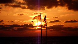 Tattered waving flag in sunset - looped Version Footage