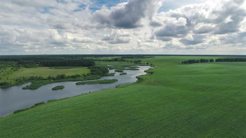 Flying Over Green Field And River stock footage