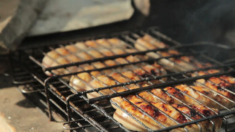 Grilled sausages over a fire at a picnic Footage
