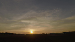 Time Lapse Sunset With Light Clouds And A Tractor Driving Back And Forth stock footage