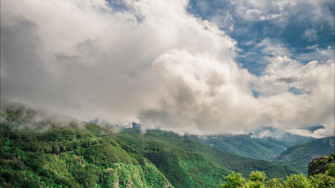 Clouds billow in the blue sky over mountains Footage