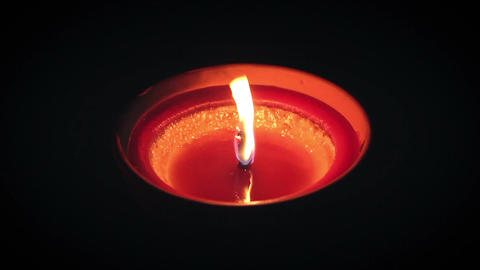 Isolated top of red candle in clay pot flickering in the dark Archivo
