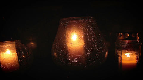 Three candles in cracked glass containers glowing in the night Archivo