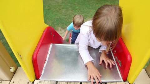 Children riding on a sliding board Live Action