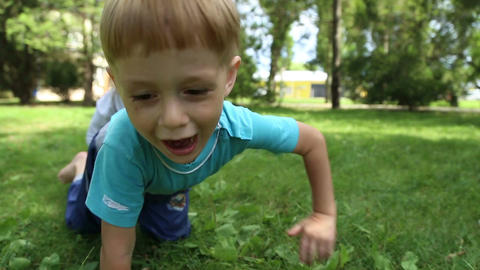 Girl and boy crawls on all fours on the grass Footage