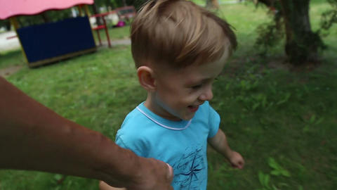 Boy runs, holding his father's hand Footage