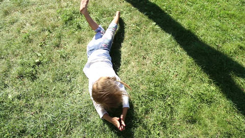 Girl and boy somersault on grass lawn Live Action