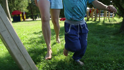 Mother and son running barefoot on the grass Live Action