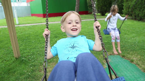 Girl and boy riding on a swing Footage