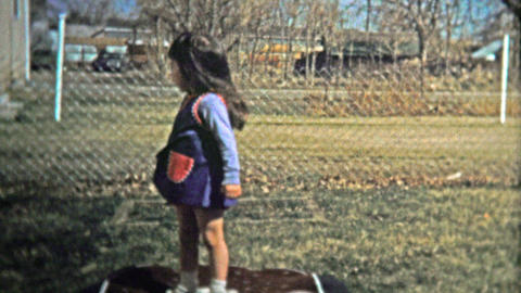 BOULDER, CO. USA - 1974: Girl practicing her jumping on small inflatable trampol Footage