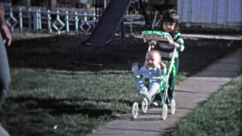 BOULDER, CO. USA - 1974: Little girl pushing baby brother around in a stoller Footage