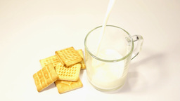 Pouring of milk to a glass and sweet cookies Footage
