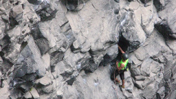 Exhausted Rock Climber Evaluating Trajectory On Basalt Rock Footage