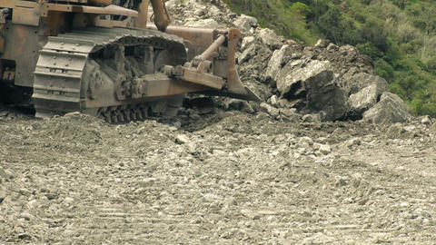 Tracked bulldozer pushing rocks low angle Footage