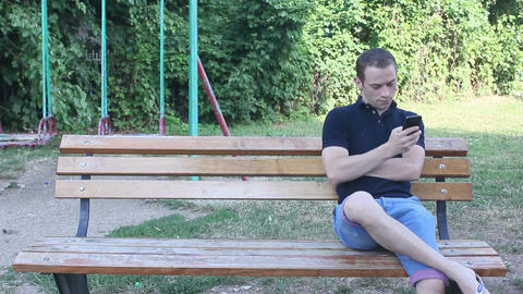 man toouching smartphone in park Live Action