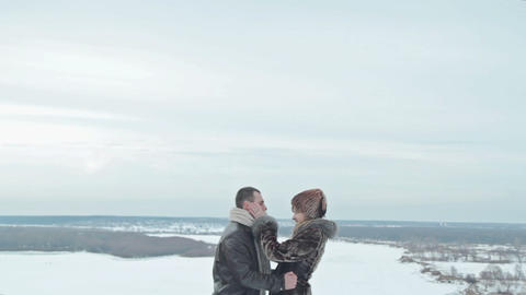 Young couple kissing by the river in winter weather Footage