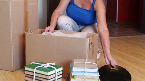 Woman Moving Into New Home And Unpacking Boxes Footage