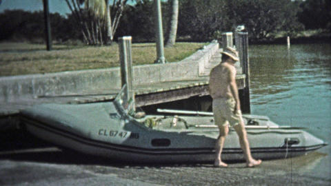 1973: Man Driving Professional Inflatable Boat Around Harbor With Pelicans stock footage