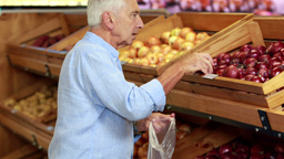 Senior man picking out apples in supermarket Footage