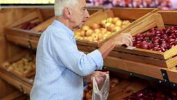 Senior man picking out apples in supermarket Footage