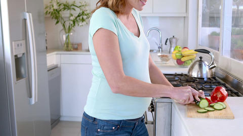 Pregnant woman preparing vegetables in kitchen Footage